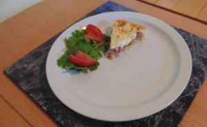 Graham's Caramelised Red Onion and Goats Cheese Tart served a small side salad of herbs and tomato wedges